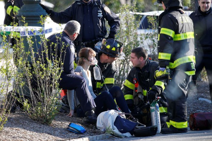 A woman is aided by first responders at the scene of an incident in lower Manhattan