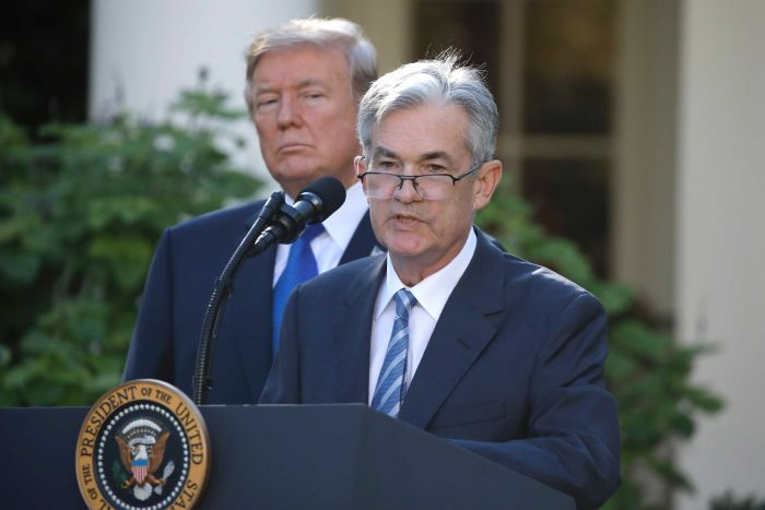 US President Donald Trump stands behind Jerome Powell as he addresses media