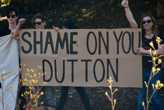 "Three women stand near bushes with a sign reading ""Shame on you Dutton"""