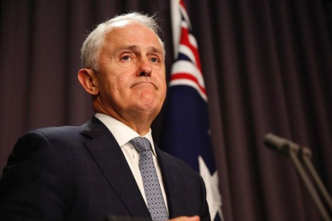 Malcolm Turnbull frowns during a press confernce, standing at a microphone in front of an Australian flag.