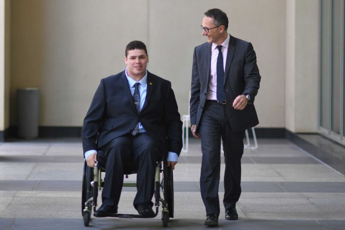 Jordon Steele-John, in his wheelchair, outside Parliament House with Richard di Natale. They are both wearing suits.