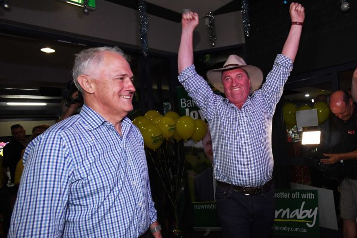 Barnaby Joyce with his arms in the air in excitement, Malcolm Turnbull stands beside him.