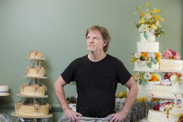 Jack Phillips stands near highly-decorated cakes.