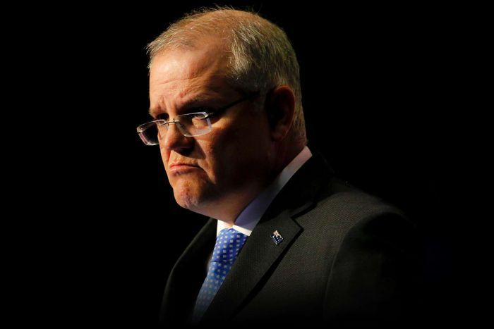 Scott Morrison frowns during a speech at Parliament House. The background is dark