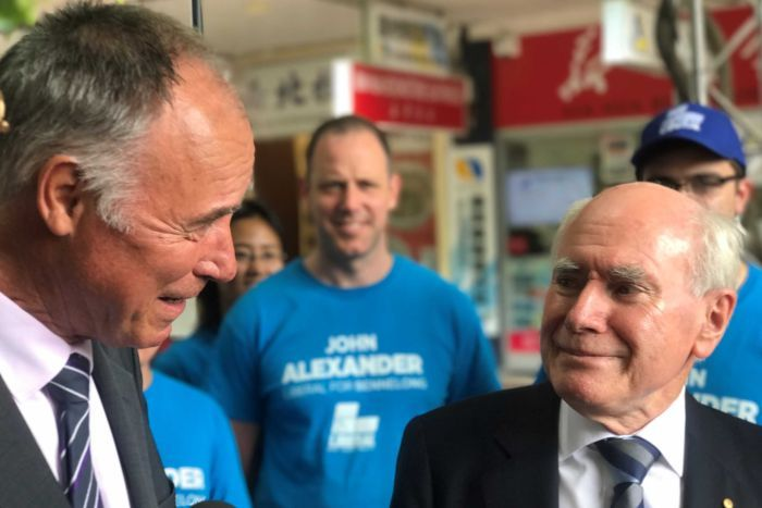 John Howard smiles, tight lipped, looking at John Alexander. Behind them are campaigners wearing blue
