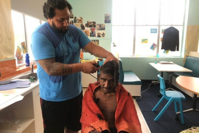 A boy sits in a chair getting his hair cut short by a man with hair clippers.