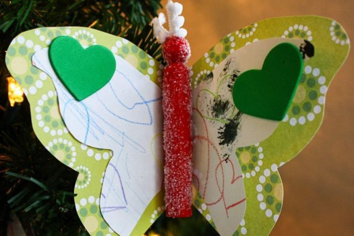 An Christmas ornament in the shape of a butterfly made from a child's artwork.