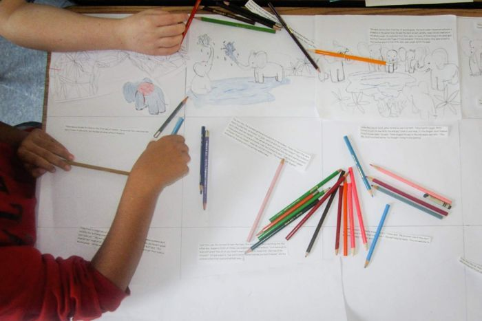 Children drawing elephants with pencils.