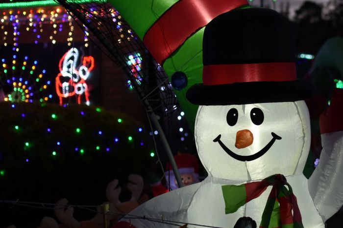 An inflatable snowman decoration in a suburban front yard.