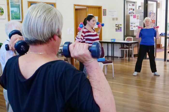 A younger female instructor leads a seniors' exercise program.