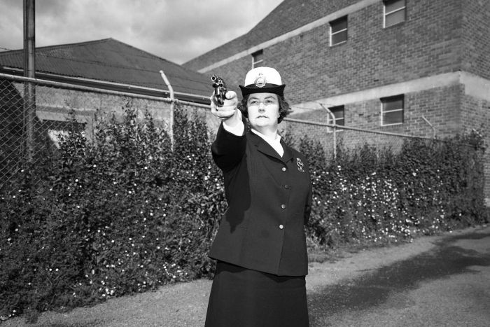 Sergeant Beth Ashlin pointing a pistol taken in the 1970s.