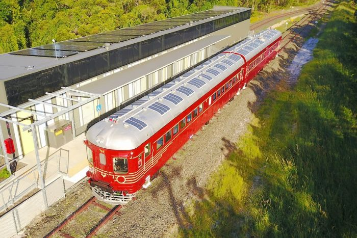 This is an aerial shot of a red and silver solar-powered train stopped at a station near Byron Bay.