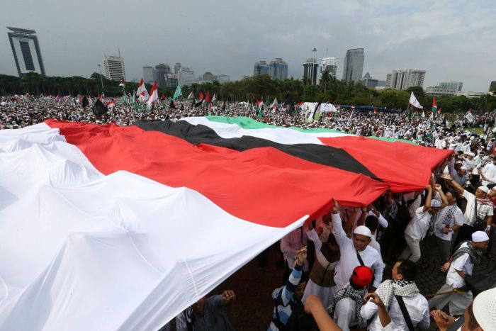 A crowd of people holding large Indonesian and Palestinian flags above their heads.