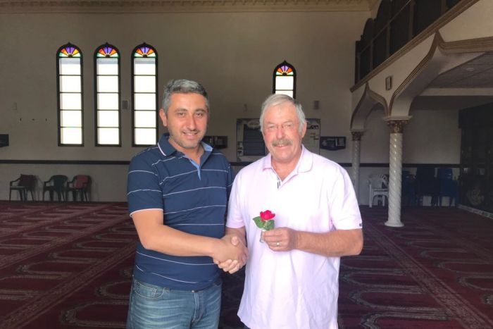 Two men shake hands inside a mosque.