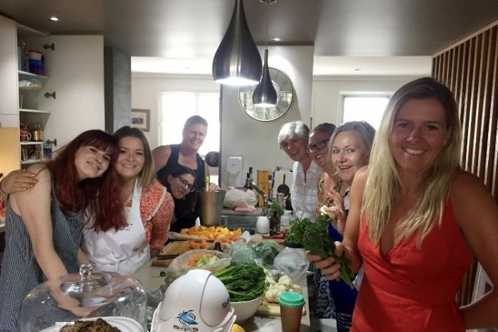 A family prepare Christmas lunch in a kitchen.