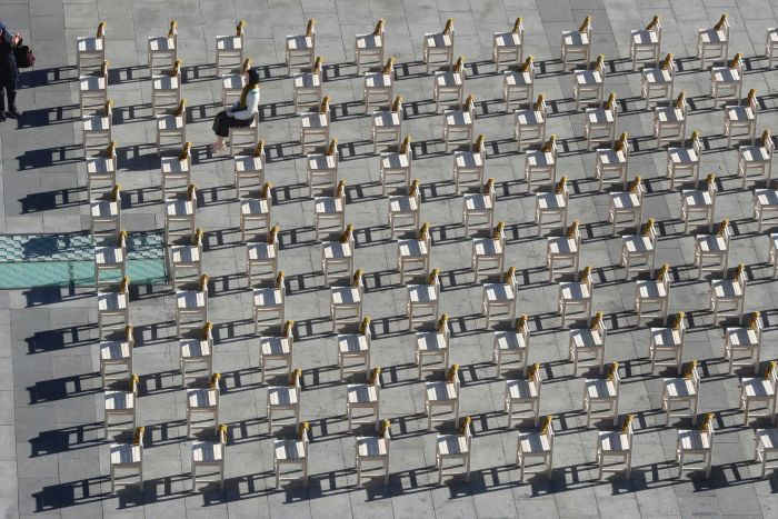 A women takes a photo of a comfort woman statue sitting a chair among rows of empty chairs symbolising victims of comfort women.