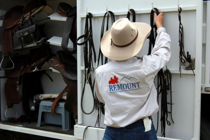 A horse owner packs up her horse's saddle