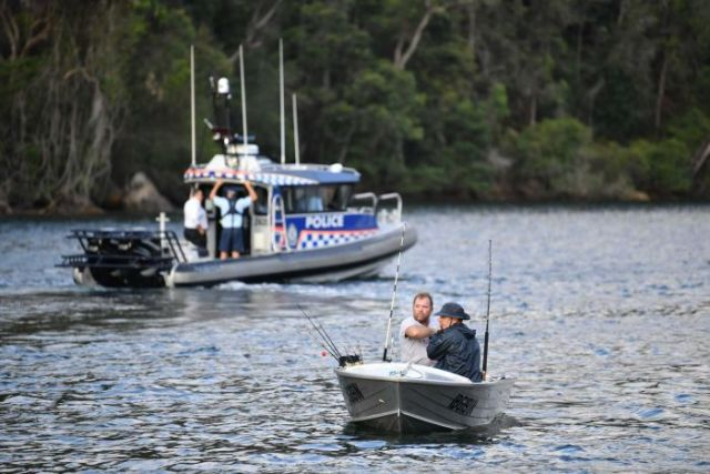 Fishermen in a dinghy travel down the Hawkesbury River with a police boat in the background.