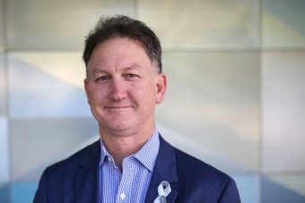 A headshot of Michael Gannon, wearing a blue jacket and white and blue shirt.