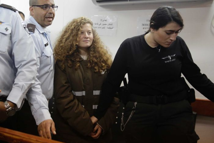Wide shot of Ahed Tamimi standing in court flanked by guards.