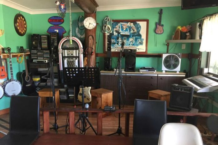 A small wooden stage set up inside the Warrell Creek Tavern with microphones and a jukebox.