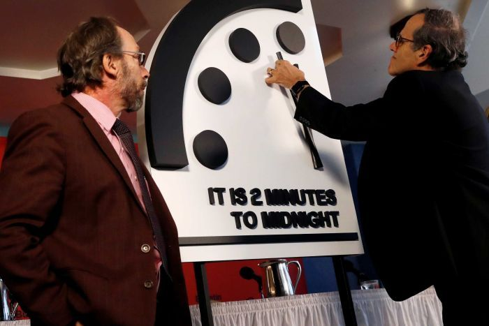 A scientist moves the hands of a model of the Doomsday Clock to two minutes until midnight.