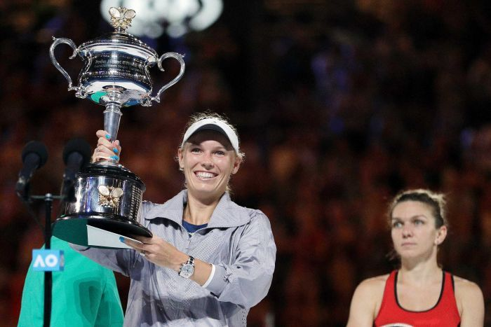 Caroline Wozniacki (L), holds trophy after beating Simona Halep (L) in the Australian Open final.