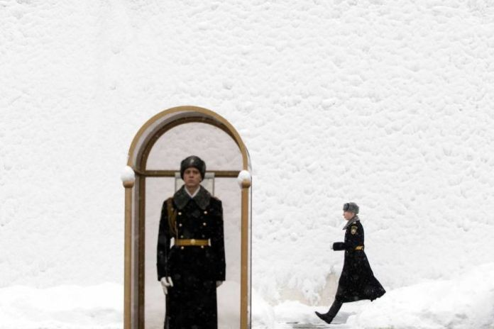 A Russian guard stands at his post outside snow covered Kremlin walls, a second guard marches behind in the snow.