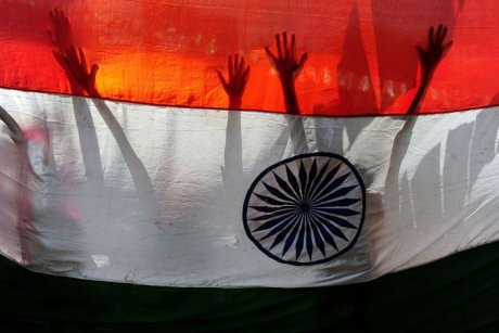 Silhouette of hands and arms behind Indian flag