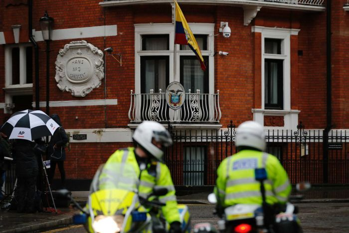 Police motorcyclists briefly stop outside the Ecuadorian embassy in London.
