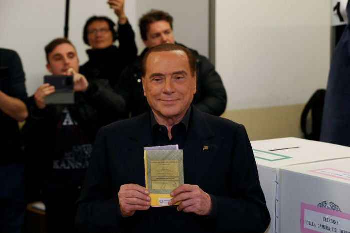 Man holds a ballot paper in front of his chest
