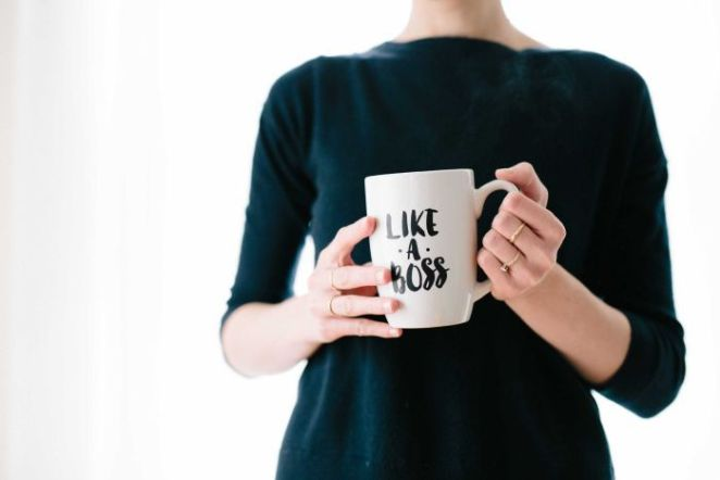 "A woman wearing a black jumper holds a mug that reads ""Like a boss""."