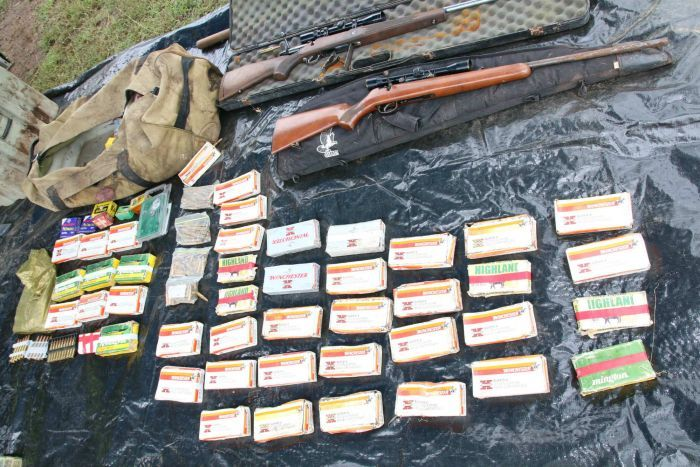 Bullets and rifles are laid out on a plastic sheet