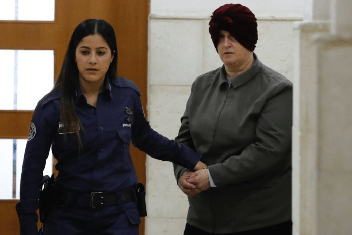 Malka Leifer is led from court by a policewoman.