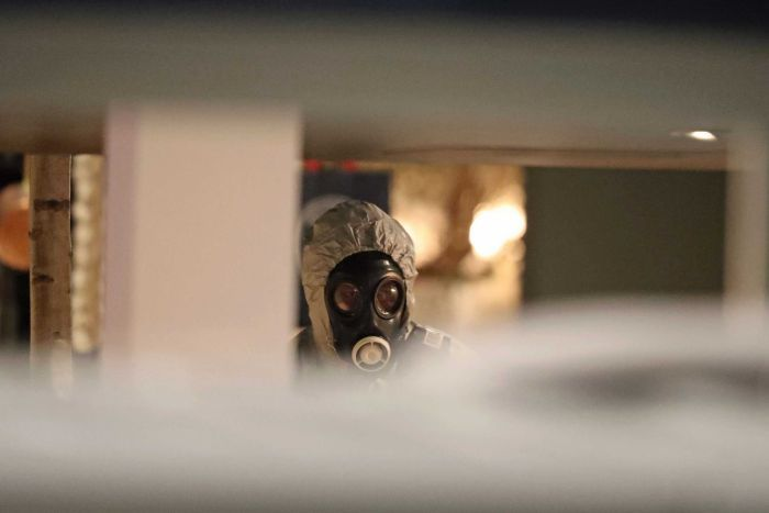 Investigators wear gas masks as they examine the restaurant