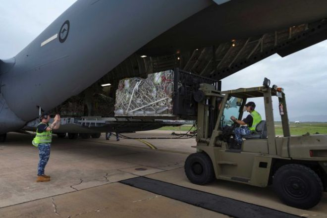 Members of the Australian Air Force use a forklift to load supplies onto a plane in Townsville.