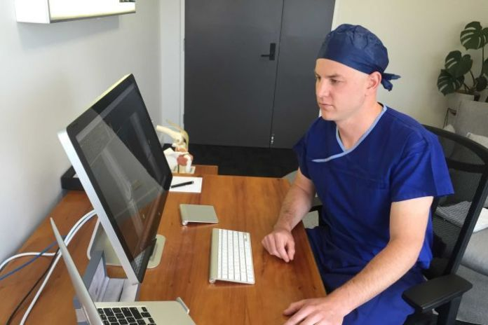 Orthopaedic surgeon, Josh Petterwood looks at a computer in his office.