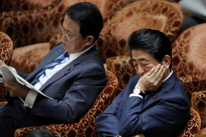 Two men sitting next to each other.