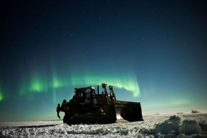 A snow grader at night, with an Aurora Australis in the night sky.