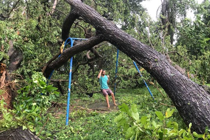 A man swings on a swingset pinned by a fallen tree in Darwin after Cyclone Marcus.