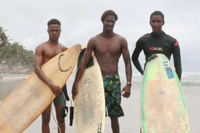 Alphonse Coulibaly (centre) and Souleymane Sidibe (right) stand on the beach with a third man and their surfboards