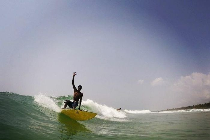 Alphonse Coulibaly surfing a wave