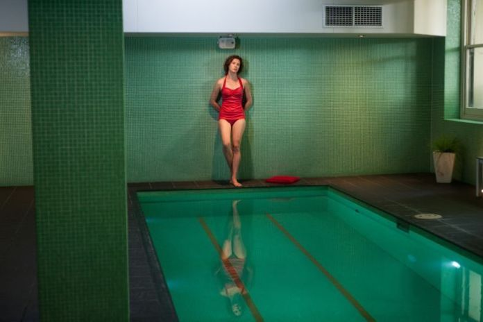 Wide shot of performed Tiffany Lyndall Knight standing by a green tiled indoor pool looking pensively into distance.