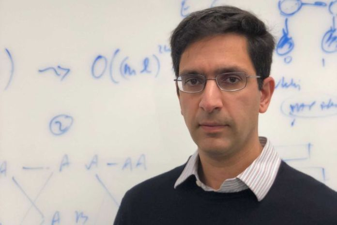 California-based Professor Lior Pachter stands in front of a whiteboard covered in maths equations
