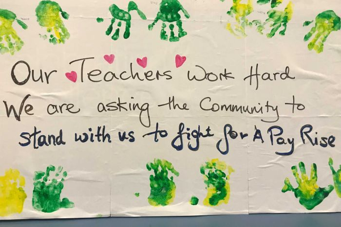 A sign bordered by children's handprints asks for support for childcare workers' fight for better pay.