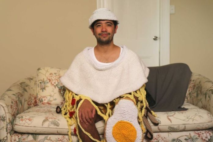 A young man in a crochet ramen noodle outfit.