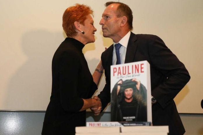 Tony Abbott and Pauline Hanson shake hands behind a copy of a the One Nation leader's book