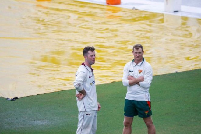 Jimmy Peirson and George Bailey speak while standing in front of wet pitch covers.