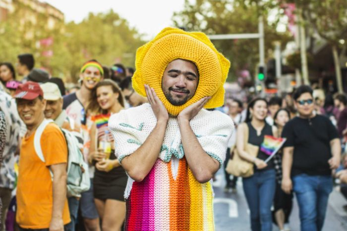A young man in a rainbow crocheted outfit at the Mardi Gras parade