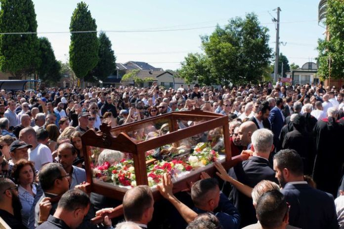 A large crowd of Maronite Catholics watching men carry a glass coffin with flowers inside.
